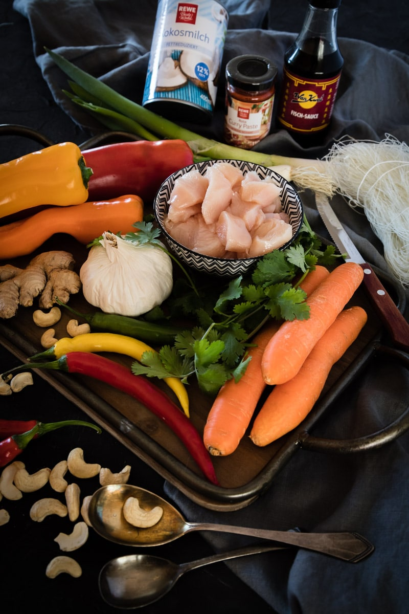Rezept für Thai Suppe mit rotem Curry, zartem Hähnchen, viel knackig frischem Gemüse, wie Pak Choi, Spitzpaprika und Brokkoli und nussigen Cashew Kernen.