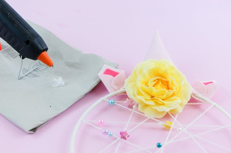DIY Einhorn Traumfänger selber basteln mit Kindern. Dieses verträumte DIY werden Kinder lieben und sind mit Freude beim Basteln dabei. Mit der einfachen und verständlichen Schritt für Schritt Anleitung gelingt das kreative und verspielte DIY Einhorn Projekt auf jeden Fall: Bild: bunten Blumen mit Heißkleber befestigen