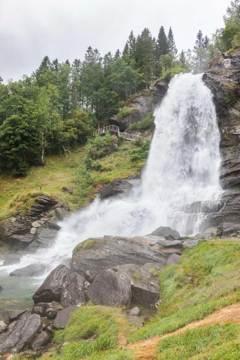 Skandinavien Roadtrip: Die Region Fjord Norwegen begeistert durch spektakuläre Fjorde, imposante Berge und tosende Wasserfälle. Ich habe euch Tipps für die schönsten Norwegischen Landschaftsrouten mit Stopps und Ausflugszielen an der Küste Fjord Norwegens zwischen Stavanger und Bergen mitgebracht. | Der Steinsdalsfossen an der Norwegische Landschaftsroute Hardanger bietet ein Blick hinter den Wasserfall.